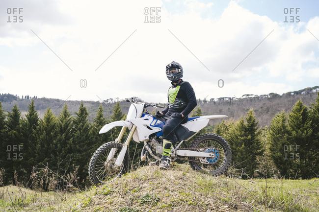 Motocross driver standing on circuit