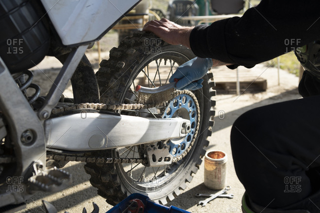 Close-up of man working on motocross bike