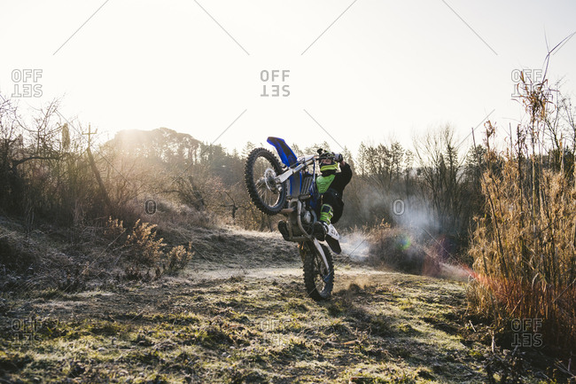 Motocross driver riding on circuit doing a wheelie