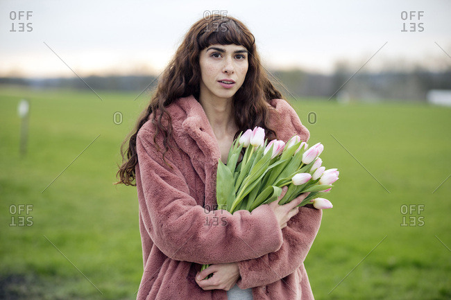Young woman with bouquet of tulips and pink coat