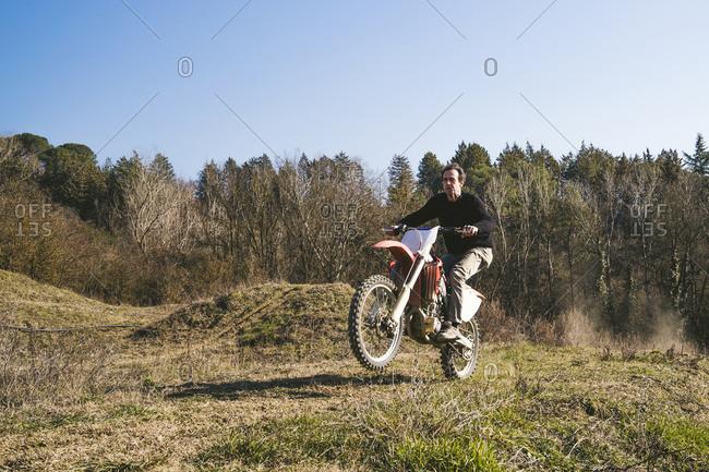 Senior motocross driver riding on circuit