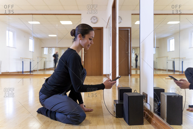 Ballet dancer using cell phone in ballet studio