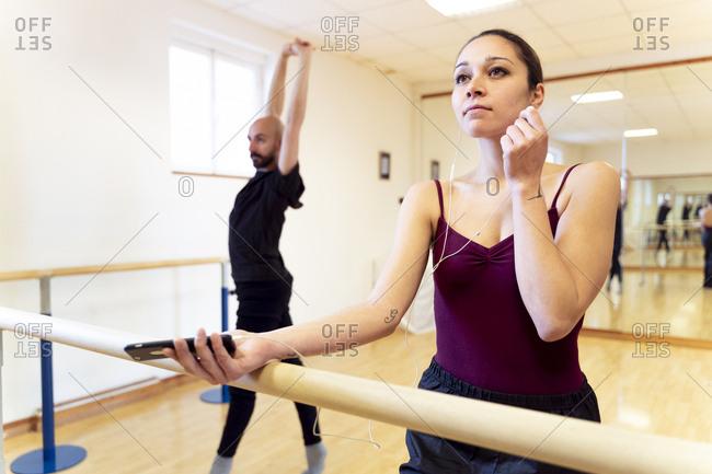 Dancing couple warming up in ballet studio