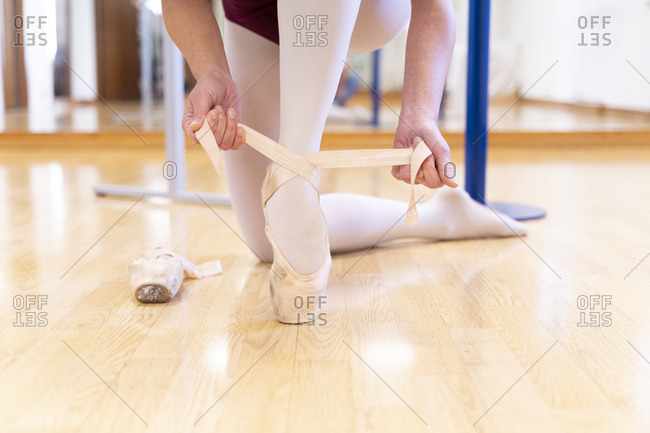 Close-up of ballet dancer putting on shoes