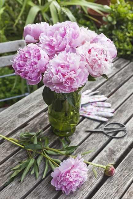 Peony bouquet in vase on garden table