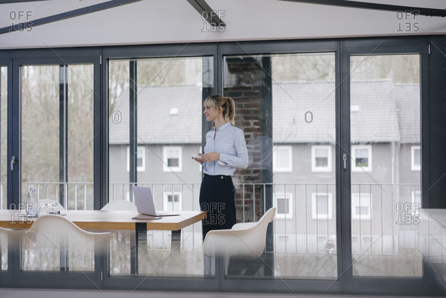 Businesswoman in boardroom- using smartphone