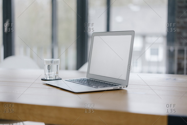 Laptop on desk in office with glass of water