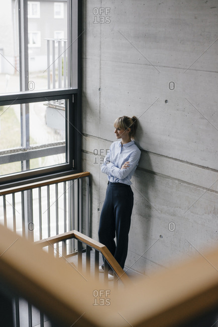 Successful businesswoman leaning on wall- looking out of window- with arms crossed