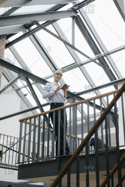 Businesswoman standing in loft office- using smartphone