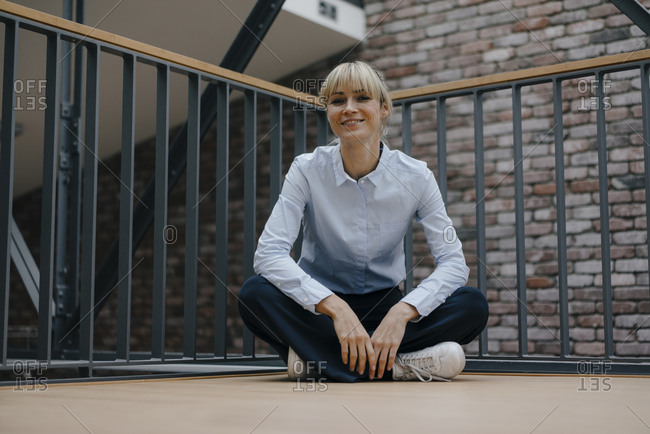 Relaxed businesswoman sitting cross-legged on the floor