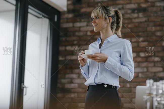 Businesswoman standing in office- taking a break- drinking coffee