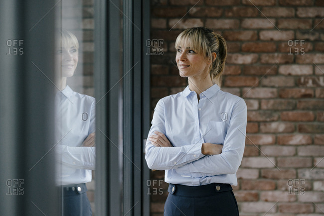 Confident businesswoman looking out of window- with arms crossed