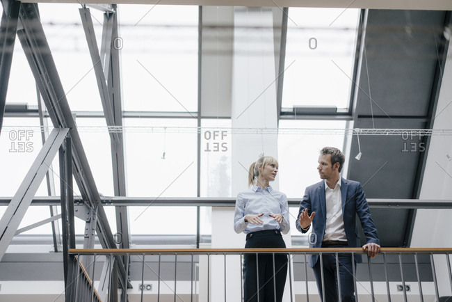 Businessman and woman standing in office building- discussing