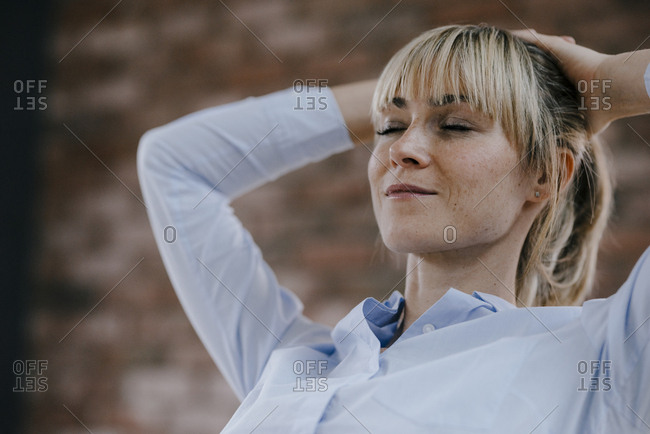 Businesswoman relaxing in office- with hands behind head