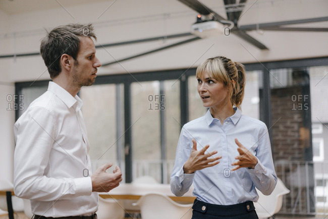 Businessman and woman standing in office- discussing