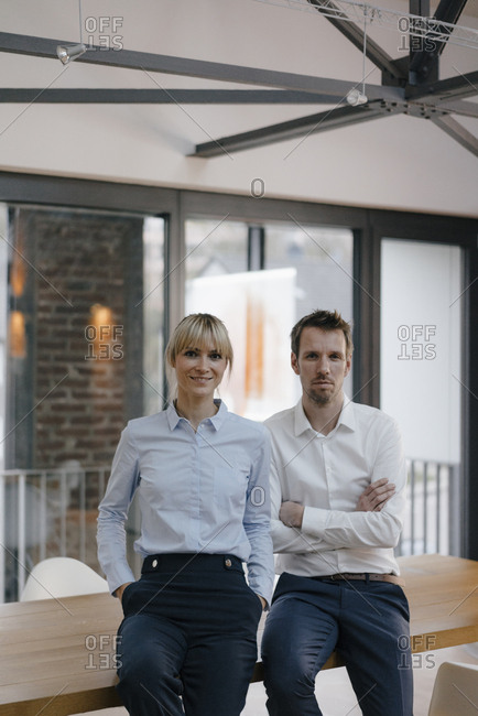 Successful businessman and woman standing in office- with arms crossed
