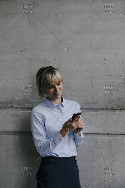 Blond businesswoman using smartphone- reading messages