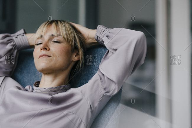 Blond woman relaxing in armchair- with hands behind head