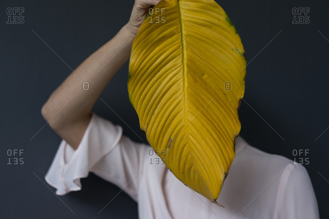 Woman covering face with a yellow banana leaf