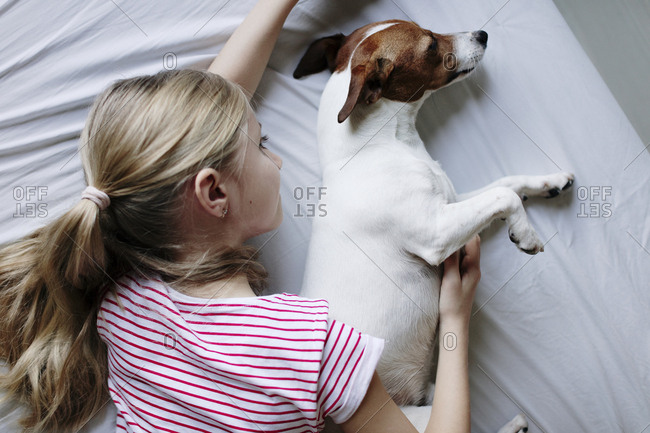 Blond girl lying on bed tickling her dog