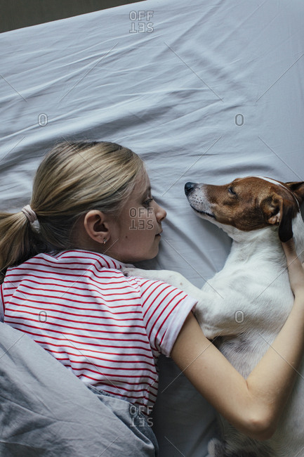 Blond girl lying on bed cuddling with her dog