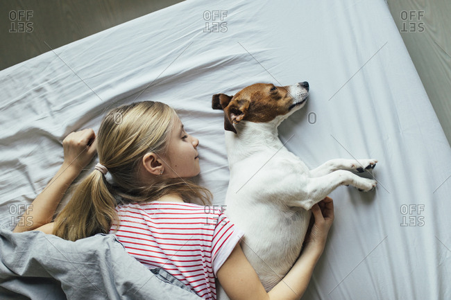 Blond girl lying on bed with her dog sleeping- top view
