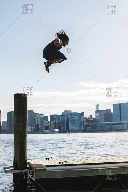 USA- New York- Brooklyn- young man doing Parkour jump from wooden pole in front of Manhattan skyline
