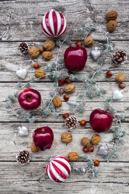 Christmas apples- walnuts- hazelnuts and Christmas decoration on wood