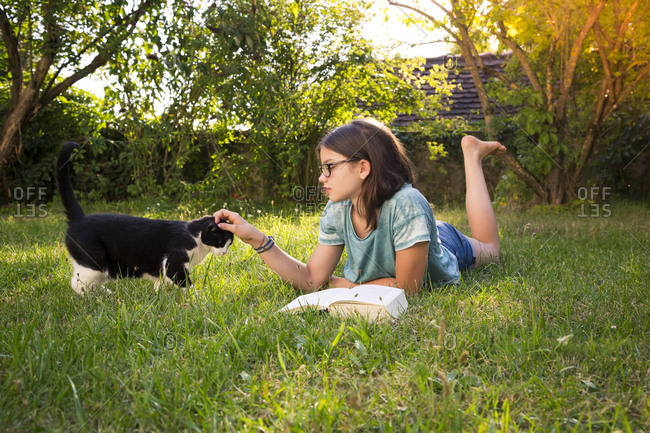 Girl with book lying on a meadow in garden tickling cat