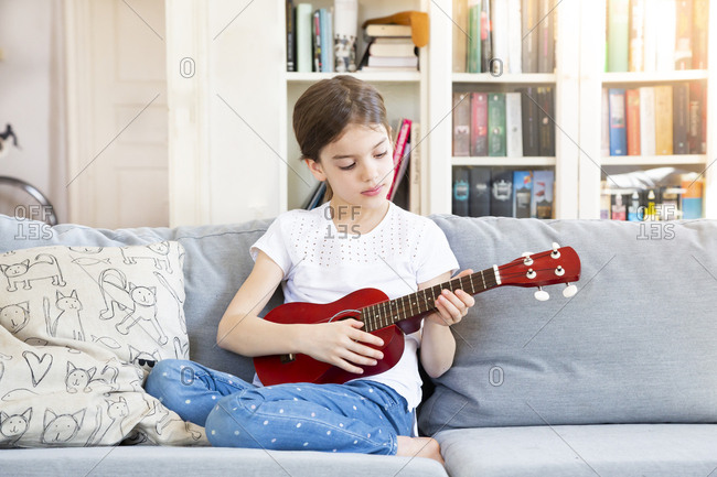 Portrait of girl sitting on couch at home playing ukulele