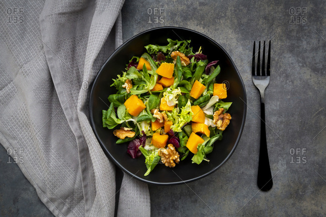 Bowl of mixed green salad with hokkaido pumpkin and walnuts