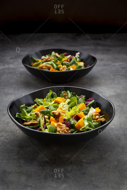 Two bowls of mixed green salad with hokkaido pumpkin and walnuts