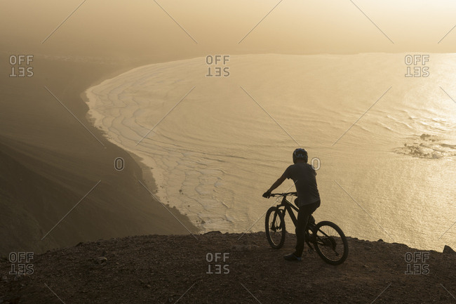Spain- Lanzarote- mountain biker on a trip at the coast at sunset enjoying the view