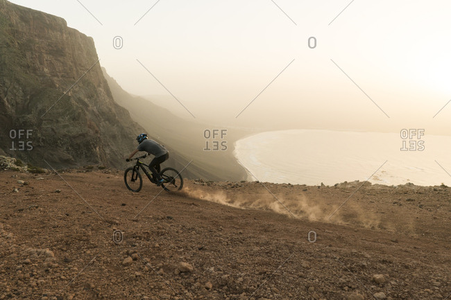Spain- Lanzarote- mountain biker on a trip at the coast at sunset