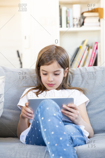 Portrait of little girl sitting on the couch at home using digital tablet