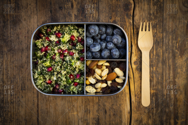 Lunchbox with bulgur herbs salad with pomegranate seeds- taboule- blueberries and trail mix