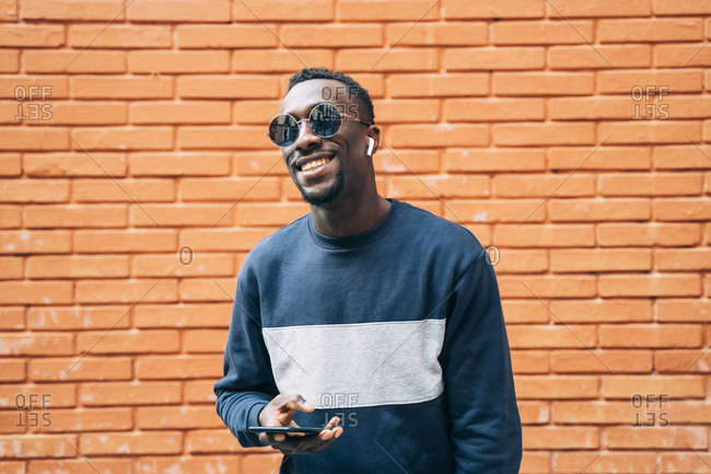 Portrait of happy man wearing sunglasses listening music with wireless earphones and smartphone
