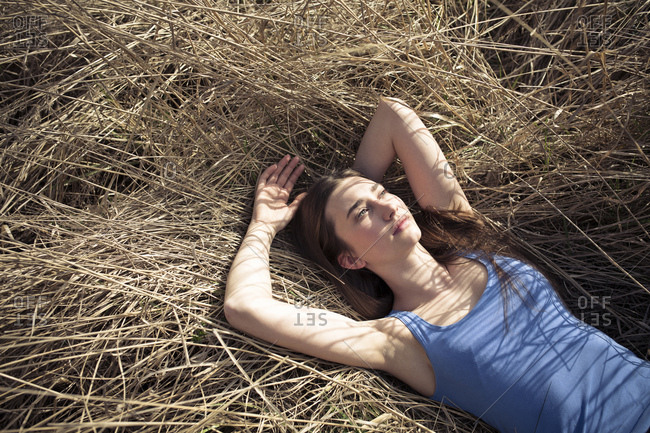 Relaxed young woman lying in meadow