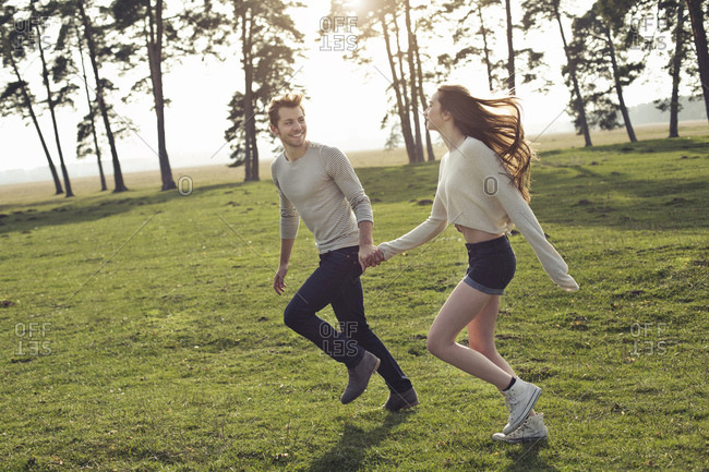 Happy young couple running hand in hand on meadow