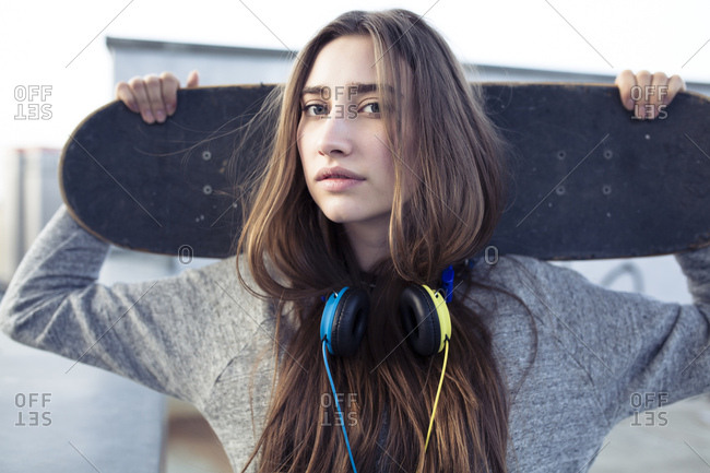 Portrait of serious young woman with skateboard and headphones