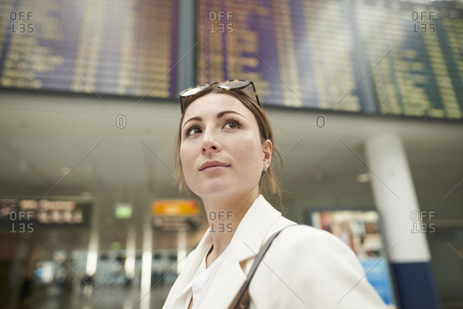 Portrait of young businesswoman at the airport under arrival departure board
