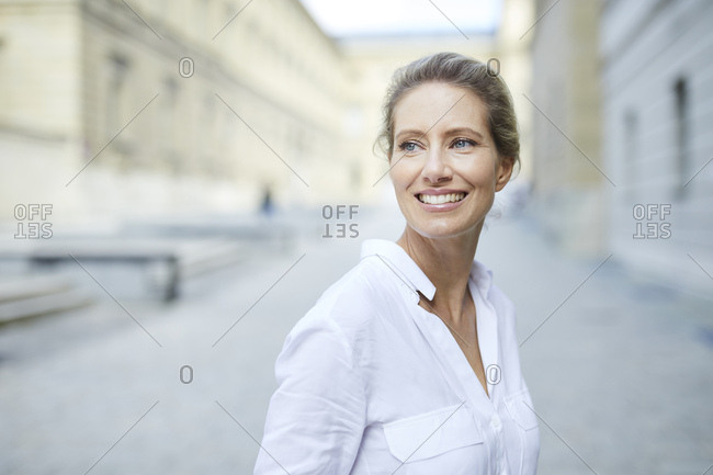 Portrait of smiling woman wearing white shirt in the city