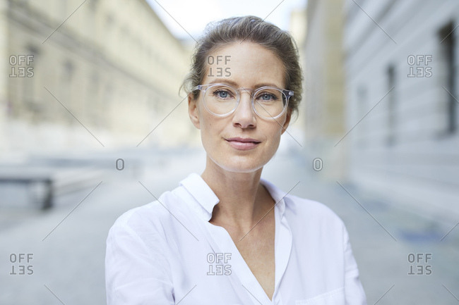 Portrait of confident woman wearing glasses and white shirt in the city