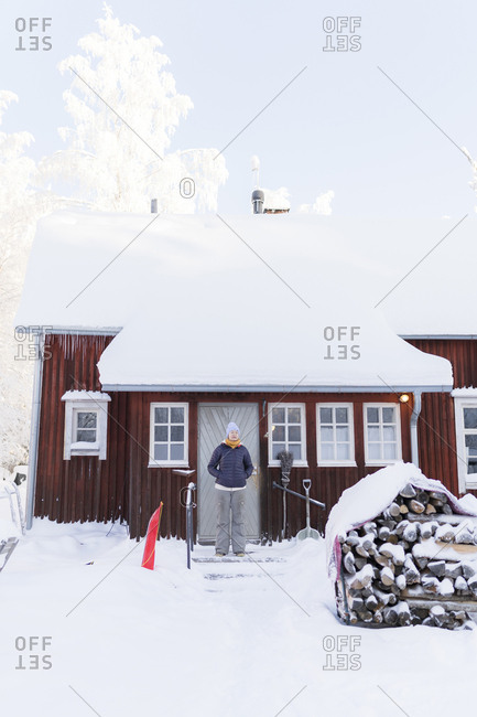 Finland- Kuopio- woman standing in front of farmhouse in winter