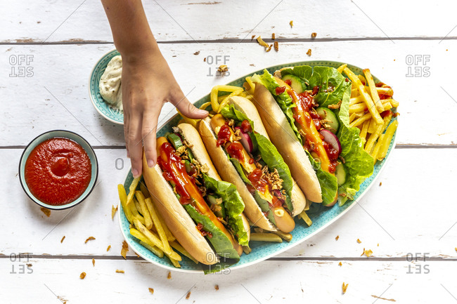 Hot dogs with french fries- ketchup and mayonnaise- hand taking an hot dog