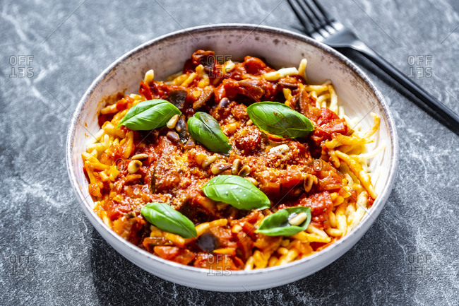 Bowl of pasta with aubergine tomato sugo garnished with pine nuts- parmesan and basil