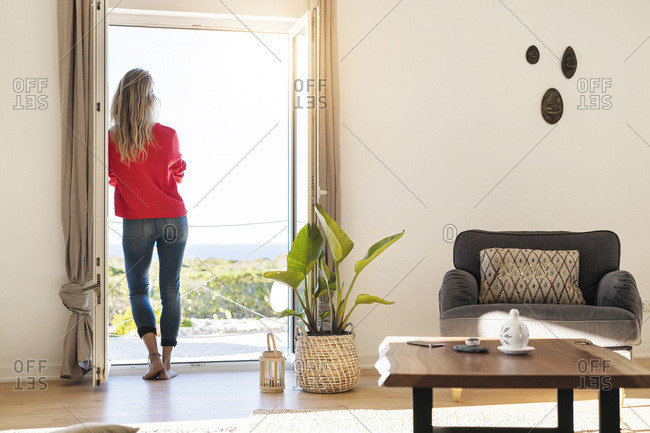 Rear view of woman leaning at open window at home looking at the sea