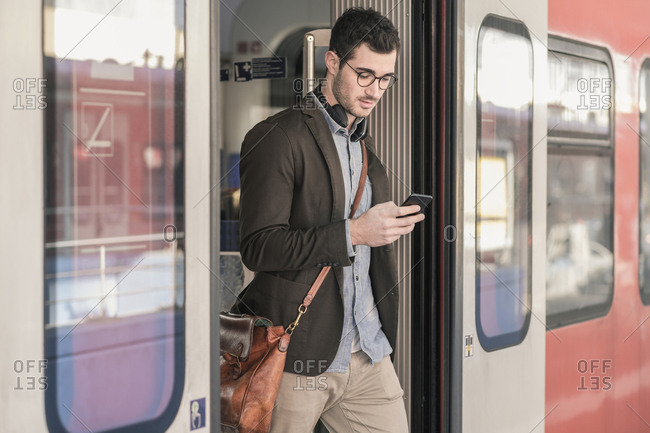 Young man using cell phone in commuter train
