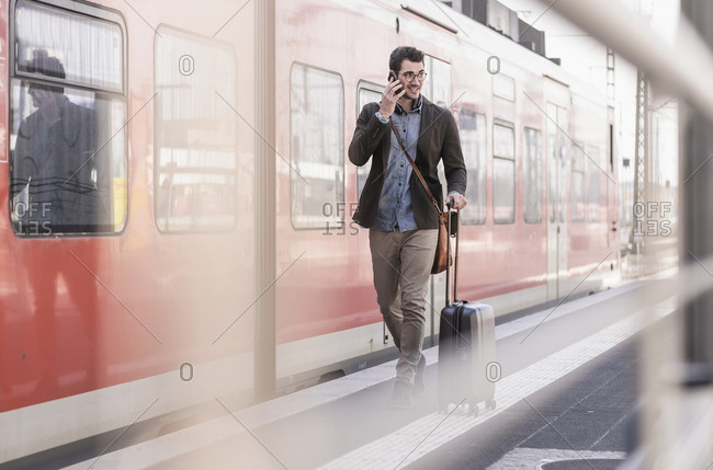 Smiling young man on cell phone walking on station platform along commuter train