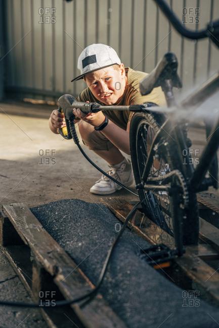 Boy washing bmx bike with pressure washer on yard
